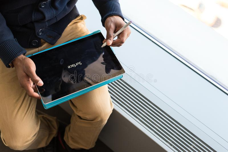 Person Wearing Brown Pants Holding Black Tablet Computer royalty free stock photography