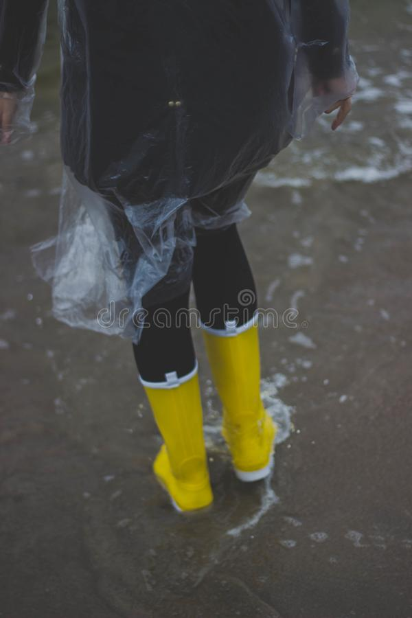 Person Wearing Clear Plastic Raincoat and Pair of Yellow Rainboots stock images