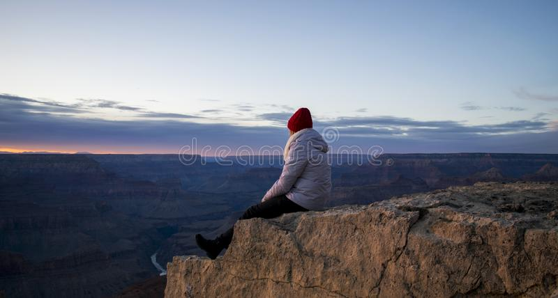 Person Wearing Gray Hooded Jacket and Black Pants Sitting on Mountain Cliff during Sunset stock photo