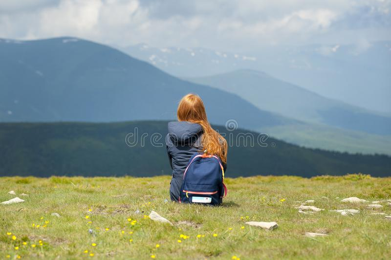 Person Wearing Gray Hooded Jacket Sitting on Grassy Field stock images