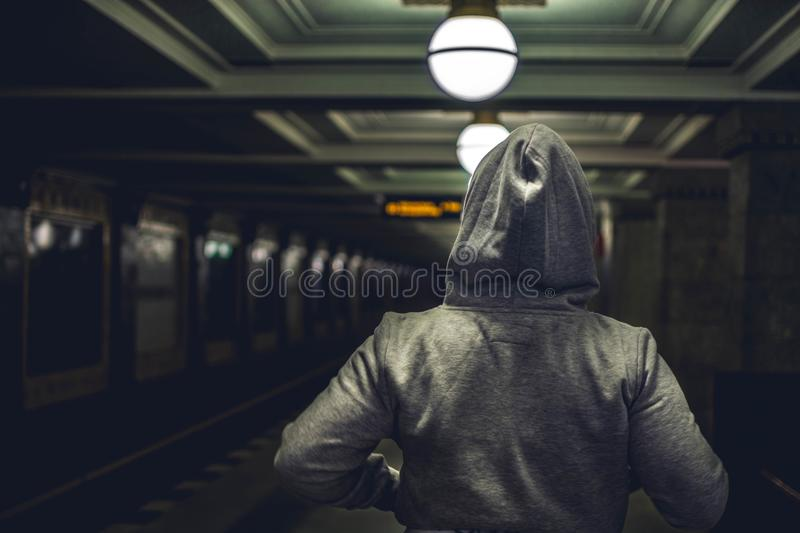 Person Wearing Gray Hooded Jacket in Train Station royalty free stock images