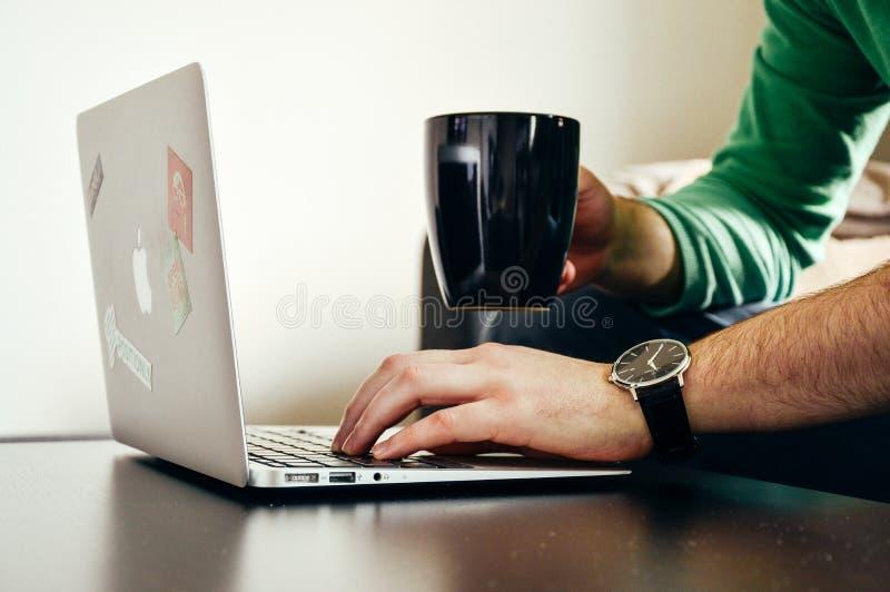 Person Wearing Green Long Sleeve Shirt Holding Black Ceramic Mug and Macbook Air stock image