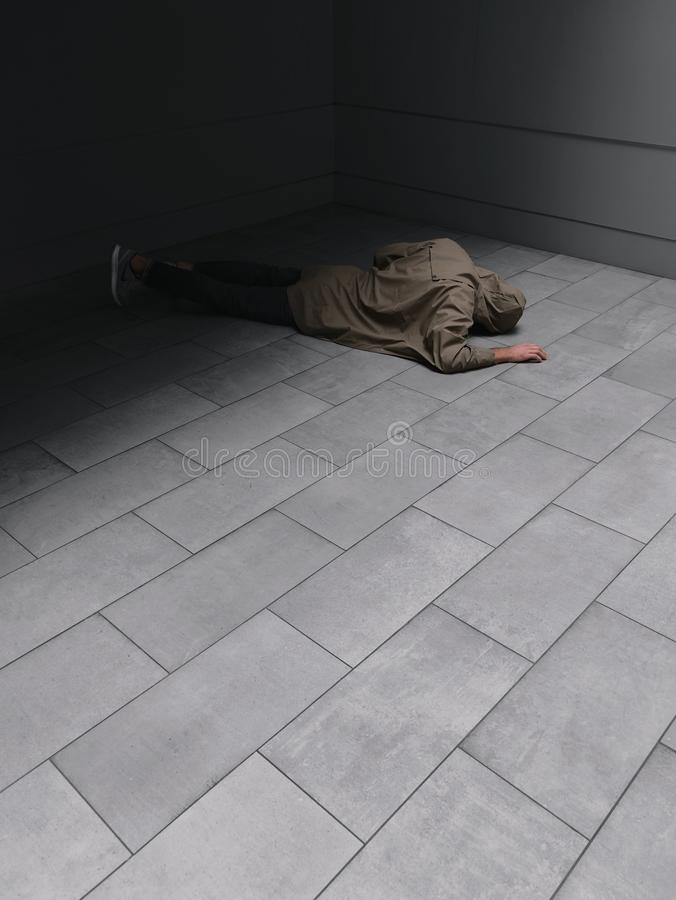Person Wearing Grey Hoodie and Black Jeans Laying on Floor stock photo