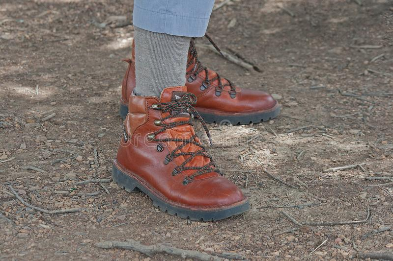PERSON WEARING HIKING BOOTS. View of pair of hiking boots on a person`s feet stock images