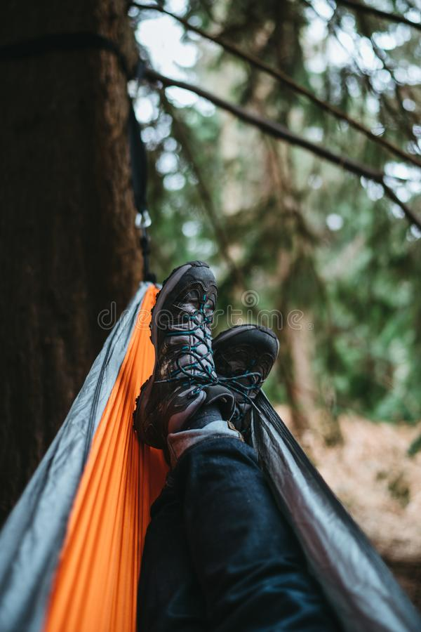 Person Wearing Pair of Black Hiking Shoes Lying on Orange and Gray Hammock stock photos