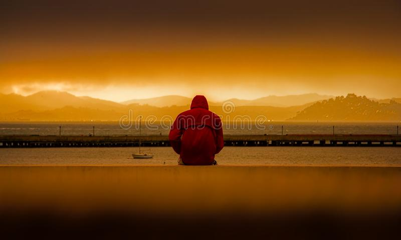 Person Wearing Red Hoodie Sitting In Front of Body of Water stock photo