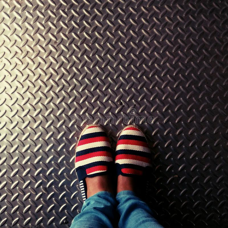 Person Wearing Red-and-multicolored Slip-on Shoes Standing on Gray Metallic Diamond Plate stock image