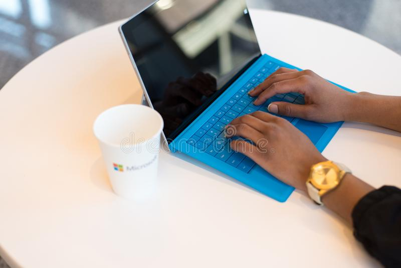 Person Wearing Round Gold-colored Watch Using Black Tablet Computer With Blue Detachable Keyboard on Round White Wooden Table royalty free stock image