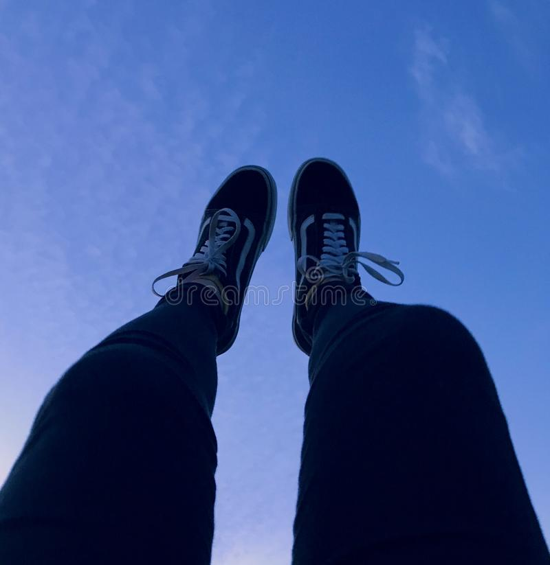 Person Wearing Vans Old Skool Sneakers Raising His Feet Pointing to They Sky royalty free stock photo