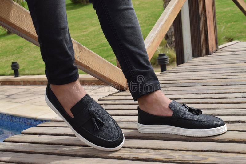 Person Wearing White-and-black Leather Slip-on Shoes With Tassels royalty free stock images