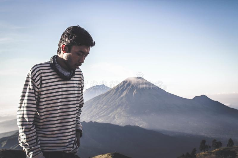 Person Wearing White and Black Striped Sweatshirt Standing in Front of Mountains stock photography