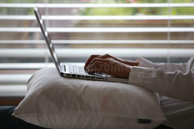 Person Wearing White Dress Shirt, der silbernen Laptop auf weißes Wurfs-Kissen verwendet lizenzfreie stockfotografie