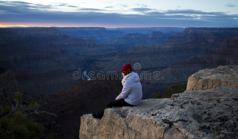 Person Wearing White Hoodie Sitting on Cliff at Daytime royalty free stock image