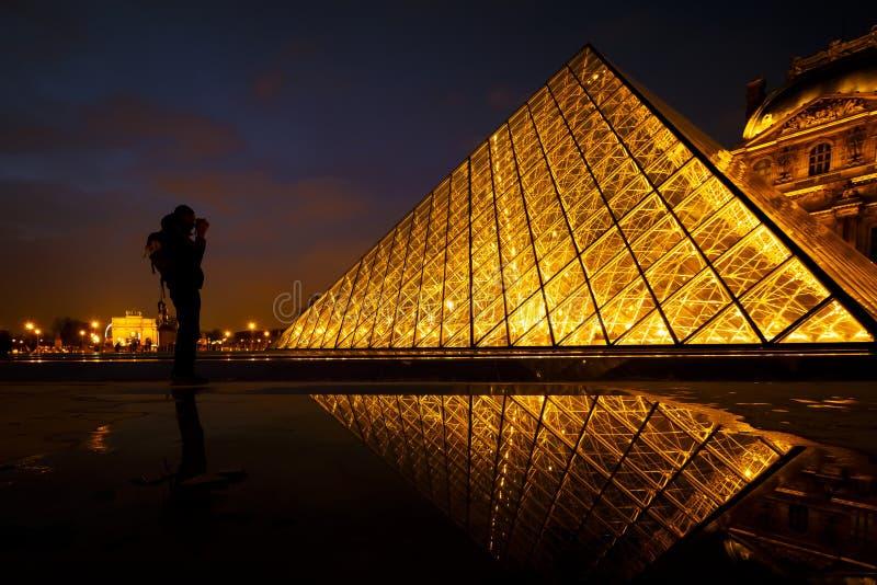 Person, welche die Pyramide am Louvre fotografiert lizenzfreie stockfotografie