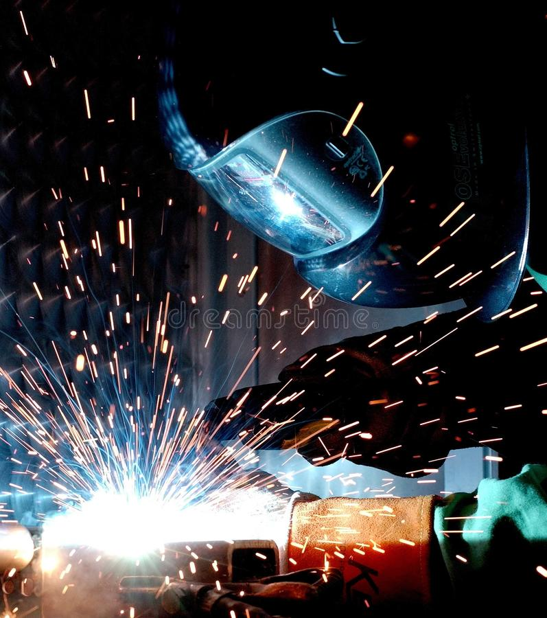 Person in Welding Mask While Welding a Metal Bar stock photo