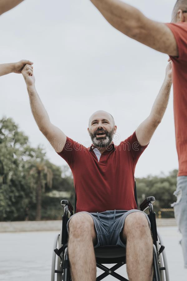 Person in a wheelchair fucks hands with his friends. Wheelchair person lays hands with their friends, they are happy, they have companionship, assist stock photos