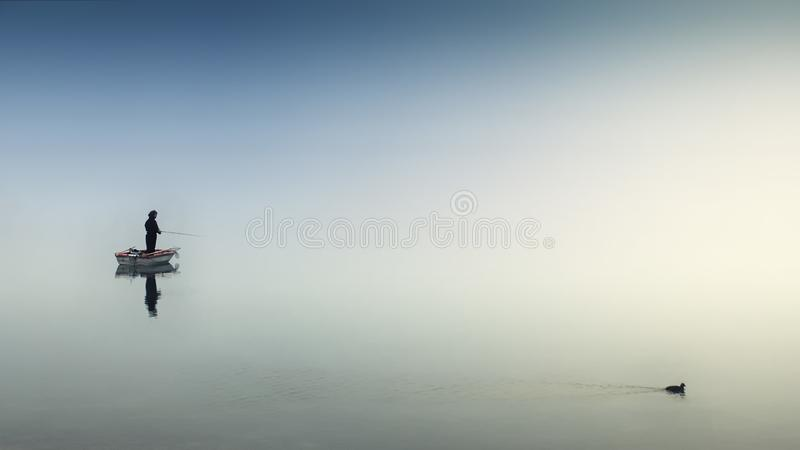 Person on White Boat Fishing on Body of Water royalty free stock images