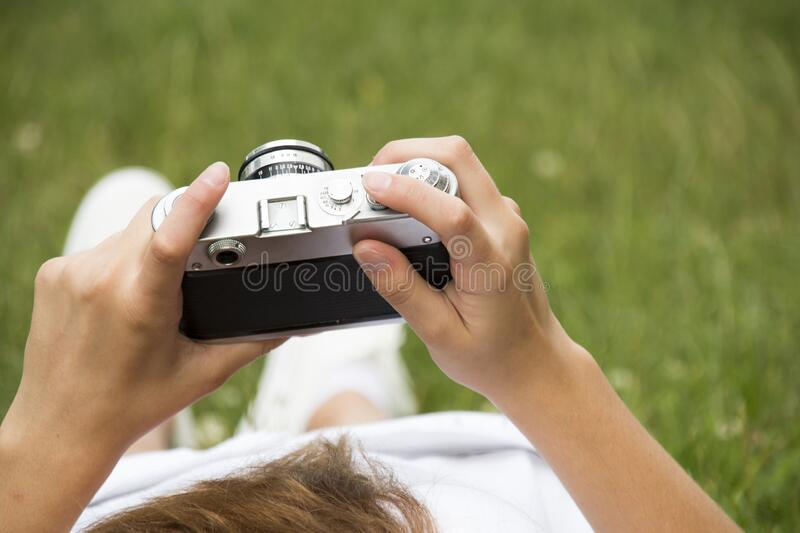 Person in White Dress Holding Grey and Black Camera on Grassland stock photography