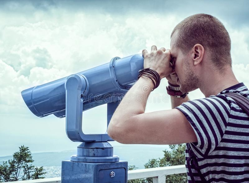 Person in White and Gray Stripes Crew Neck T Shit Using Telescope Near White Metal Handrails Under White Clouds during Daytime royalty free stock photos