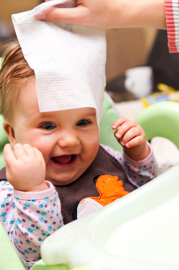 Person wiping head of baby royalty free stock photo