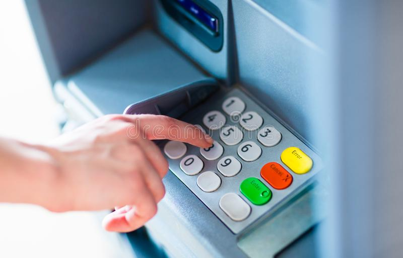 A person withdrawing money from a atm machine stock image