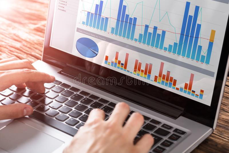 Person Working With Graphs On bärbar dator arkivbild