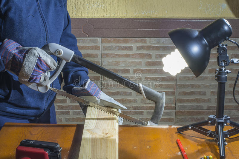 Person working with a saw on wood. Working gloves person cutting off in the wood royalty free stock image