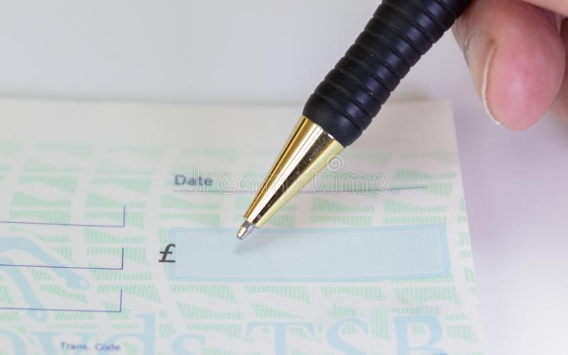 Person signing check with pen in cheque book royalty free stock image