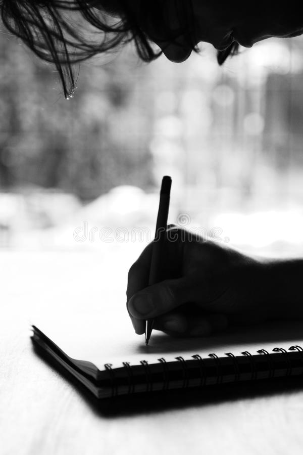 Person writing on notepad. Black and white image of a person writing on a notepad royalty free stock photo