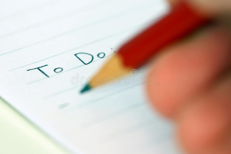 Person writing to do list stock image
