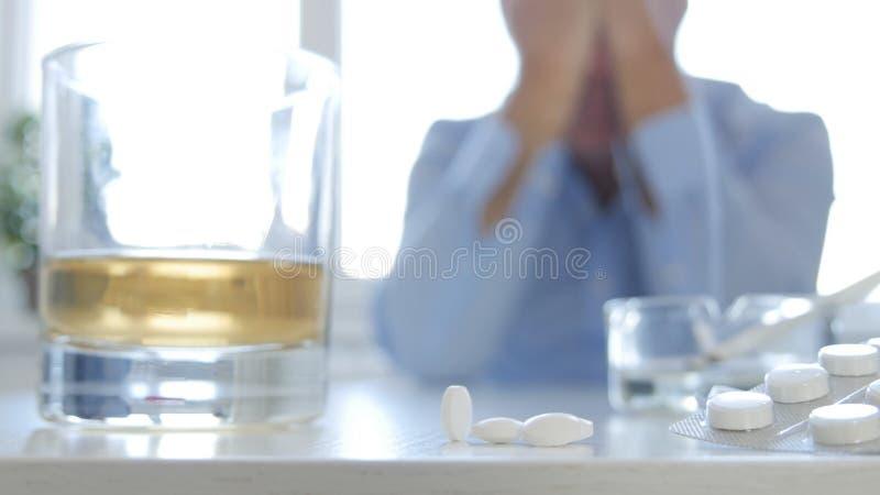 Persona adicta que hace píldoras peligrosas del alcohol y de la toma de la bebida del humo de la combinación fotos de archivo