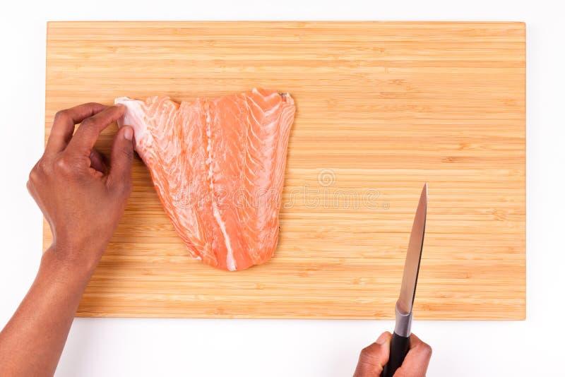 Persona afroamericana de la mujer que prepara salmones imagen de archivo libre de regalías