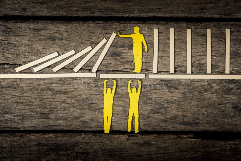 Persona amarilla que soporta bloques que caen imagen de archivo