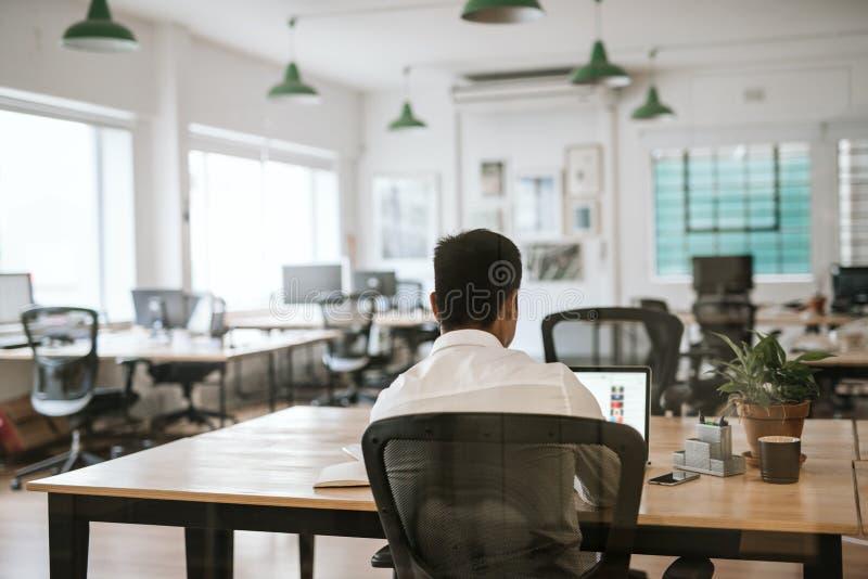 Persona anónima del negocio que trabaja en un ordenador portátil en el escritorio de oficina imagen de archivo