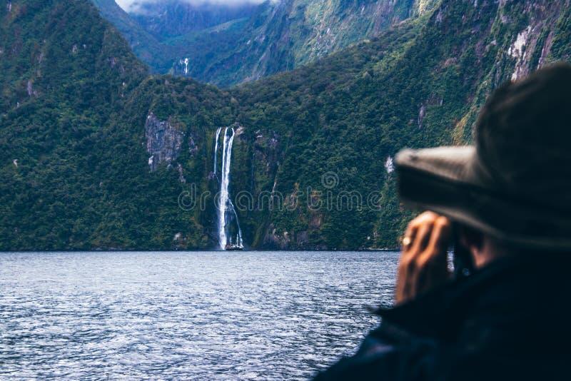 Persona anónima que toma imágenes de la cascada imagen de archivo
