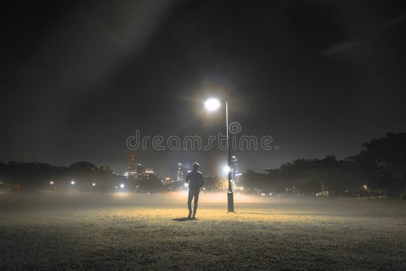 Persona anonima che cammina vicino alla lampada di via fotografie stock libere da diritti