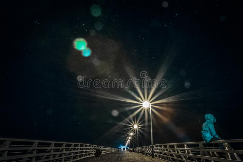 Persona anonima che si siede sull'inferriata sul ponte alla notte immagine stock