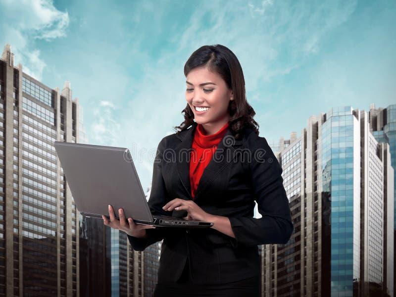 Persona asiática del negocio que mecanografía en el ordenador portátil foto de archivo libre de regalías