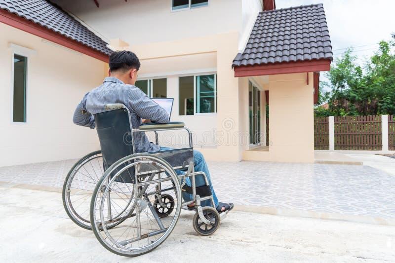 Persona asiatica di medio evo disabile nel lavoro della sedia a rotelle a casa con il computer portatile immagine stock libera da diritti