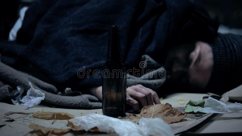 Persona borracha que duerme en la calle urbana fr?a en la noche, el abuso de alcohol y el apego imagen de archivo