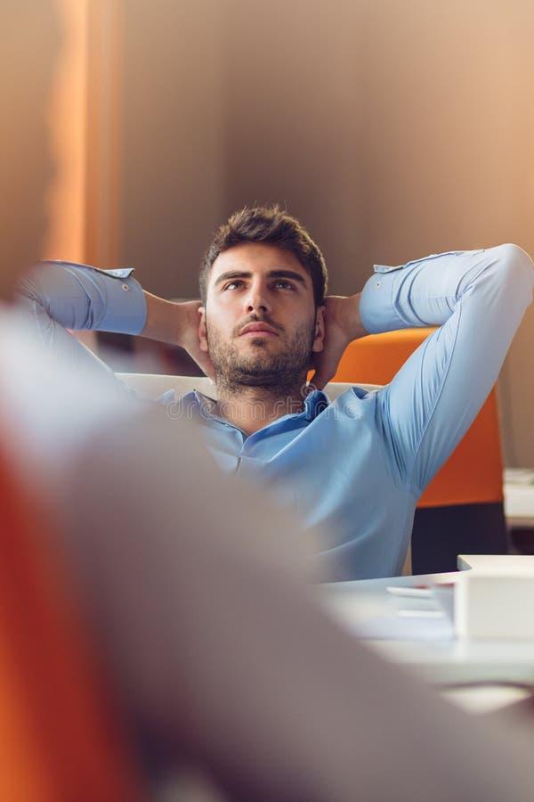 Persona caucásica del negocio que se sienta en manos que sueñan despierto de pensamiento de la oficina detrás de la cabeza fotos de archivo libres de regalías