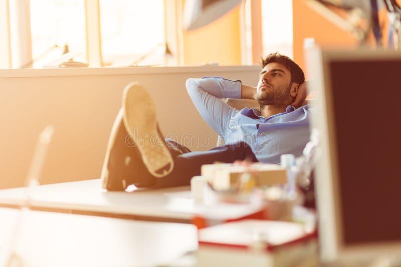 Persona caucásica del negocio que se sienta en manos que sueñan despierto de pensamiento de la oficina detrás de la cabeza imagen de archivo libre de regalías