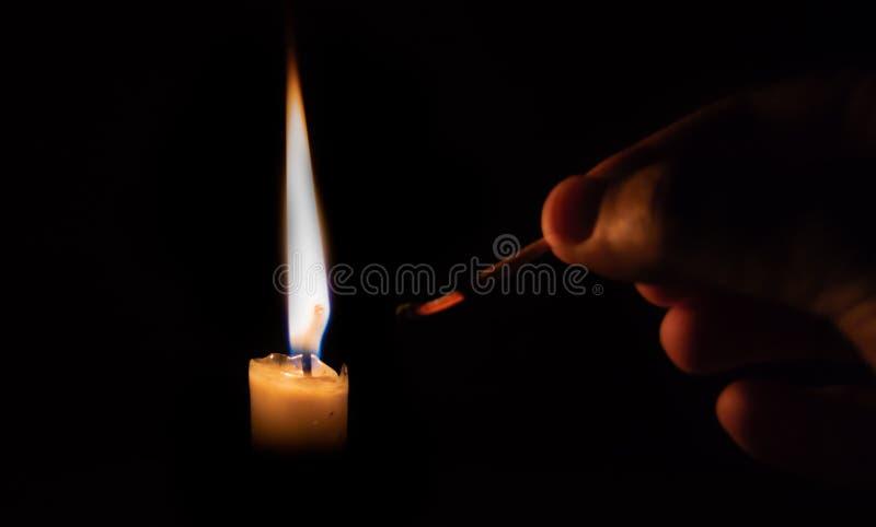 Persona che accende una candela con un fiammifero circa per estinguere il fiammifero immagini stock