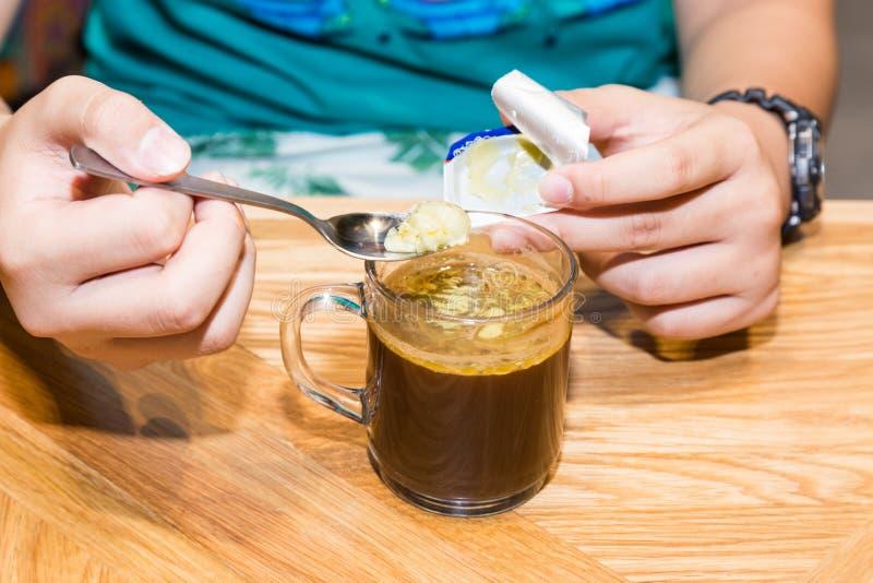 Persona che aggiunge burro al caffè immagini stock libere da diritti
