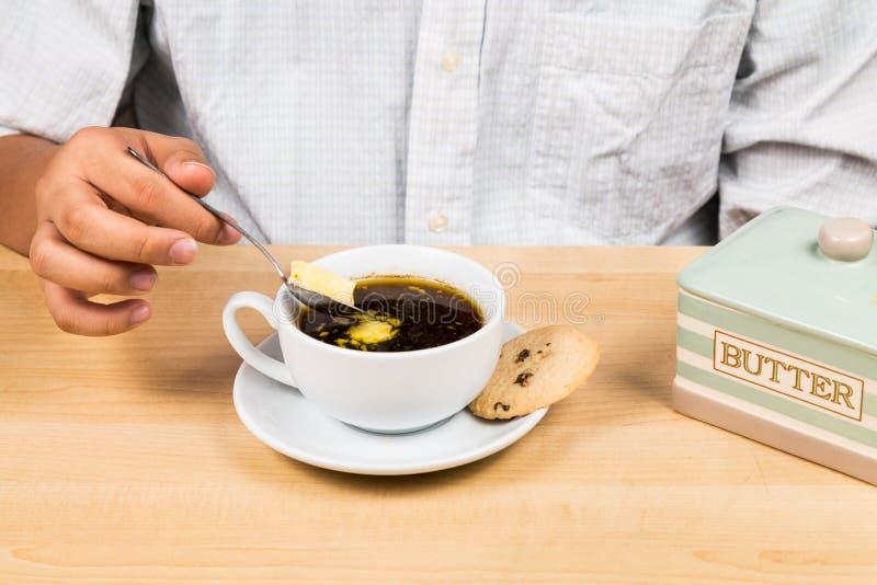 Persona che aggiunge burro al caffè fotografia stock