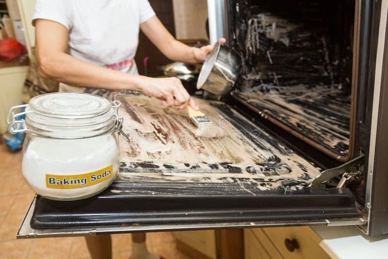 Persona che applica il bicarbonato di sodio misto su superficie del forno fotografie stock libere da diritti