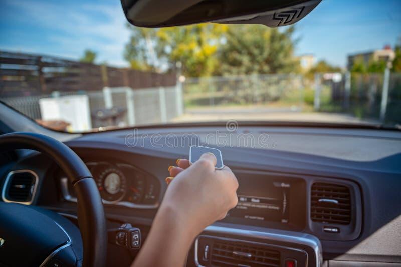 Persona che apre il portone automatico della proprietà con telecomando immagine stock libera da diritti