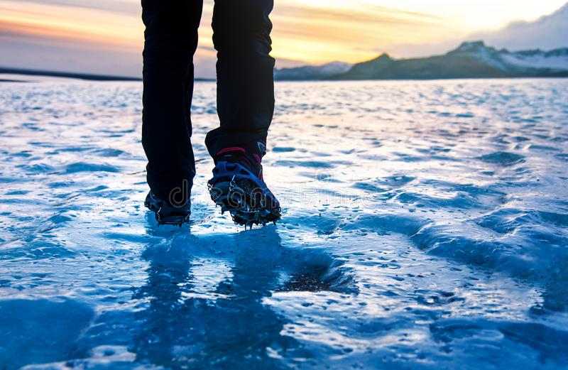 Persona che cammina sui ramponi d'uso della superficie del ghiaccio del ghiacciaio immagine stock libera da diritti