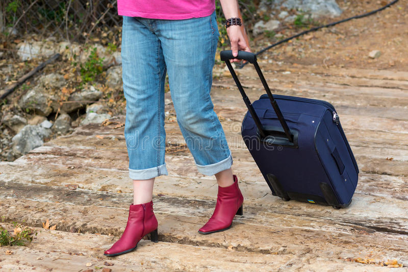 Persona che cammina sul vecchio ponte di legno che tira la valigia di viaggio immagini stock libere da diritti