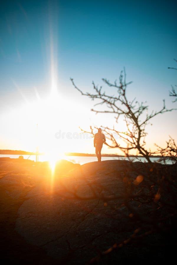 Persona che cammina verso il tramonto fotografia stock